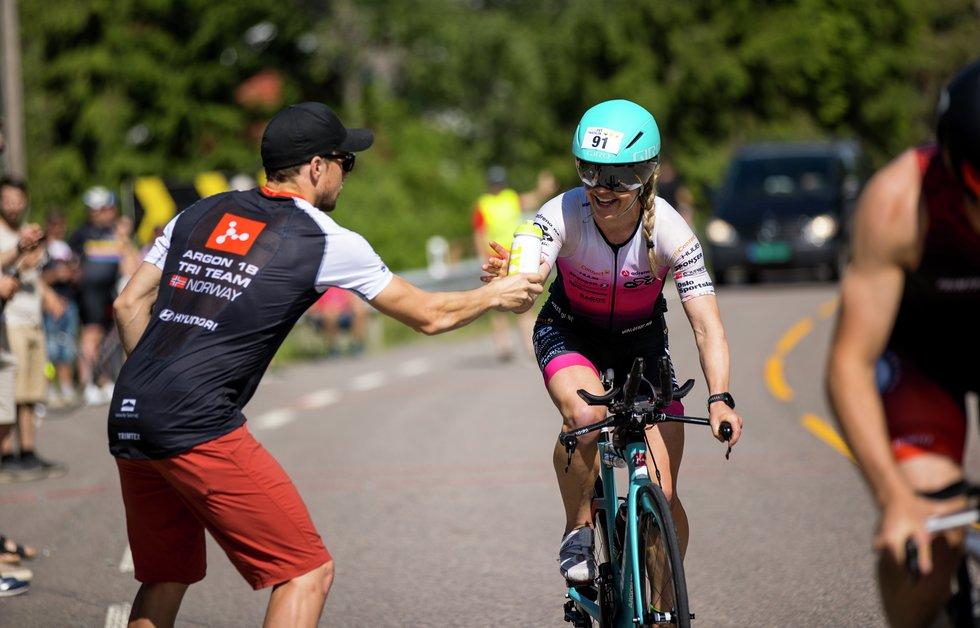 Julie Aspesletten mottar drikke etter den første sykkelrunden. Hun mente sykkeldelen var høydepunktet i dag. (Foto: Sylvain Cavatz)