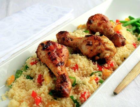 Oppskriftsbilde av couscoussalat med grønnsaker og kylling servert på hvitt fat.