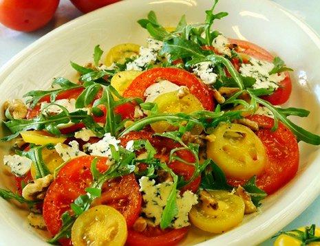 Tomatsalat med røde tomater og gule cherrytomater servert på hvit tallerken