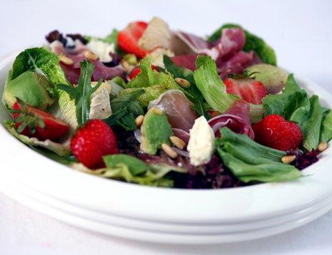 Salat med jordbær, melon og avokado på hvit tallerken