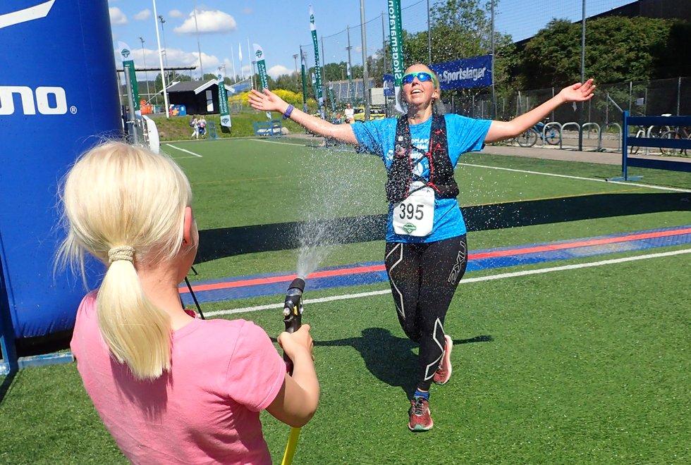 Linda Øverberg får en avkjølende dusj av sin datter Johanne etter målgang på maratondistansen under Nordmarka Skogsmaraton 2019