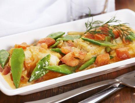 Fiskekarri med tomater på hvitt fat