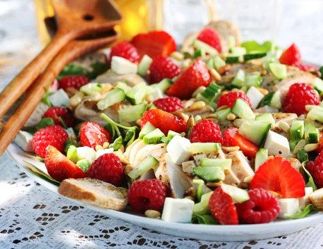 Miljøbilde av sommersalat med jordbær og bringebær på blondeduk.