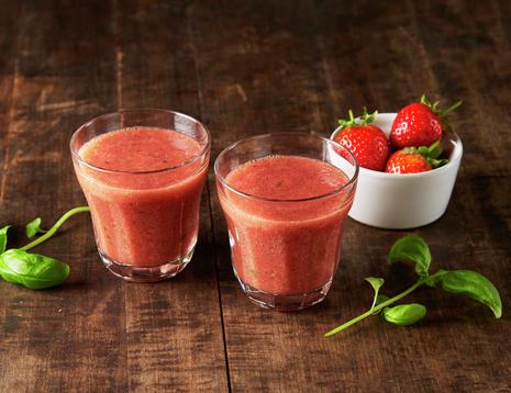To glass rød smoothie på brun bakgrunn