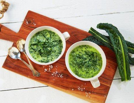 To skåler med suppe med svartkål på en brun fjøl