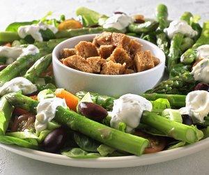 Oppskriftsbilde av aspargessalat med sprøstekte brødkrutonger servert på hvitt fat.
