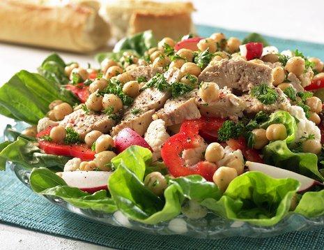 Salat med reddik, paprika og kikerter servert på glassfat