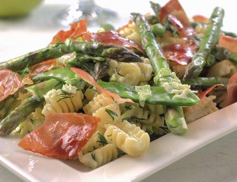Pasta med asparges og sukkererter på hvit tallerken