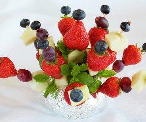 Fruktspyd i rødt, hvitt og blått - med jordbnær, melon, slåbær og druer. Dekorativt til 17. mai-bordet.