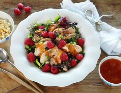 Oppskriftsbilde av kyllingsalat med bringebær servert på hvit tallerken.