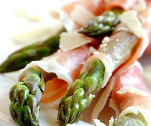Asparges med skinke servert på hvit tallerken