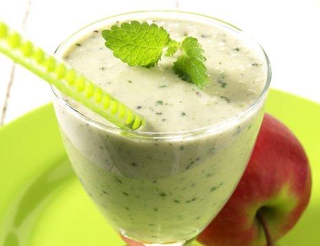 Et glass grønn smoothie på grønn asjett