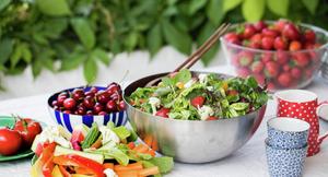 Bord med sommermat; bær, tomater og salater