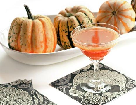 Juice laget av gresskar servert i martiniglass med pyntegresskar i bakgrunnen.