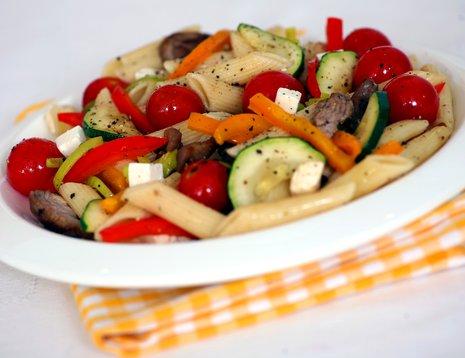 Pastasalat med tomat, paprika og gulrot servert på hvit tallerken