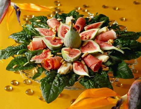 Miljøbilde av salat med fiken dandert som en blomst på glassfat.