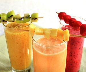 Tre ulike smoothie i glass med fruktspyd på toppen