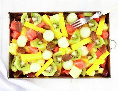 Miljøbilde av fruktsalat med kiwi, melon og druer.