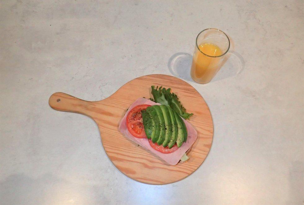 Frokost med ristet brød med skinke, salat, tomat og avokado. Drikke: Appelsinjuice