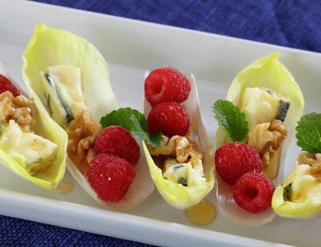 Oppskriftsbilde av hjertesalatblader med bringebær, blåmuggost og nøtter servert på fat.