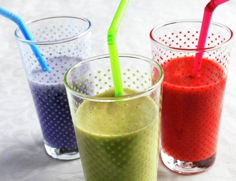 Tre glass smoothie i ulike farger med sugerør