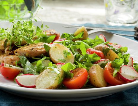 Potetsalat med tomater servert på hvitt fat.
