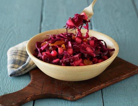 Oppskriftsbilde av rødkålsalat med rosiner og epler servert i dyp keramikkskål.