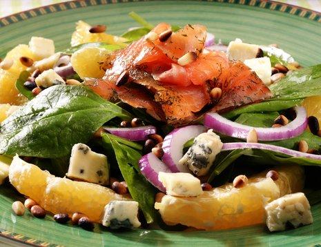 Oppskriftsbilde av salat med laks og rødløk servert på grønn tallerken.