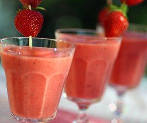 Tre glass smoothie i høye glass med jordbær