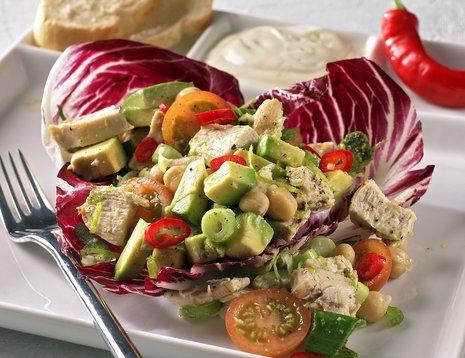 Kyllingsalat med rødkål, avokado og tomat servert på hvit tallerken