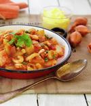 Gryte med tomater, gulrøtter og poteter servert i panne
