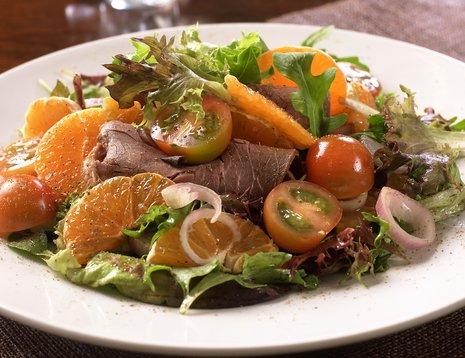Oppskriftsbilde av roastbiffsalat med appelsin, cherrytomater og rødløk servert på hvit tallerken.