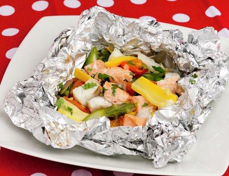 Grønnsaker og fisk i folie på rødprikkete duk