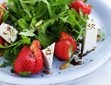 Ruccola med jordbær og fetaost på hvit asjett